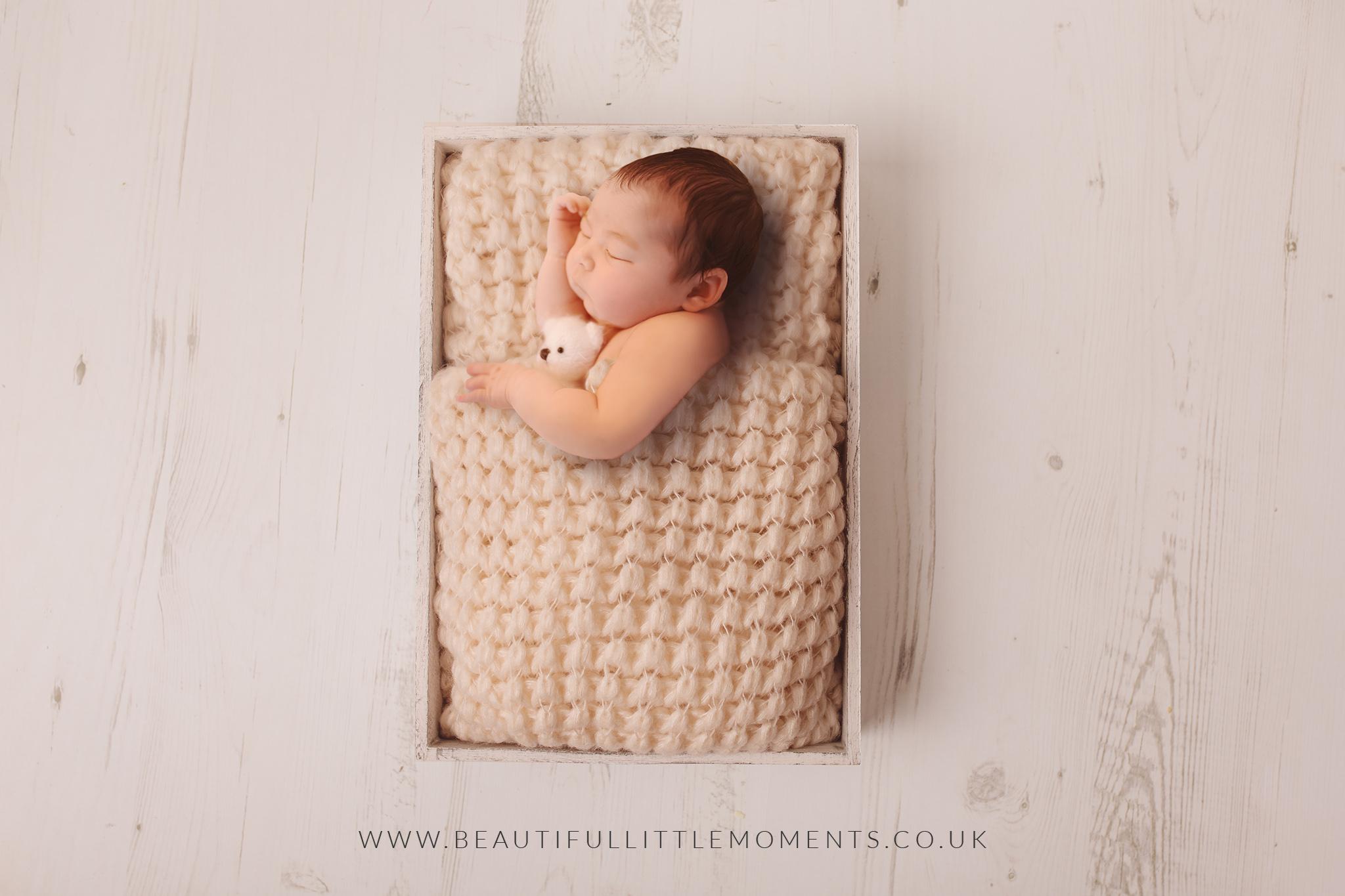 newborn-girl-in-bed-cream